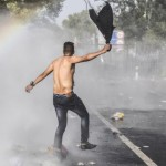 a-refugee-gestures-as-hungarian-riot-pol