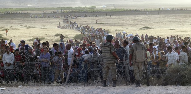 turkish-soldiers-stand-guard-syrian-refugees-wait-behind-border-fences
