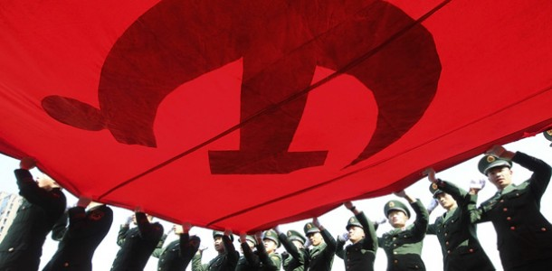 paramilitary-policemen-hold-their-fists-and-raise-a-giant-flag-of-communist-party-of-china-as-they-attend-an-oath-taking-rally-to-ensure-the-safety-of-the-upcoming-18th-national-congress-of-the-commun