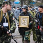 armed-pro-russian-protesters-escort-a-comrade-who-is-carrying-an-icon-which-they-said-was-found-in-the-seized-office-of-the-sbu-state-security-service-in-luhansk
