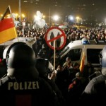 people-attending-an-anti-immigration-demonstration-organised-by-pegida-walk-past-opponents-of-pegida-behind-police-cars-in-dresden